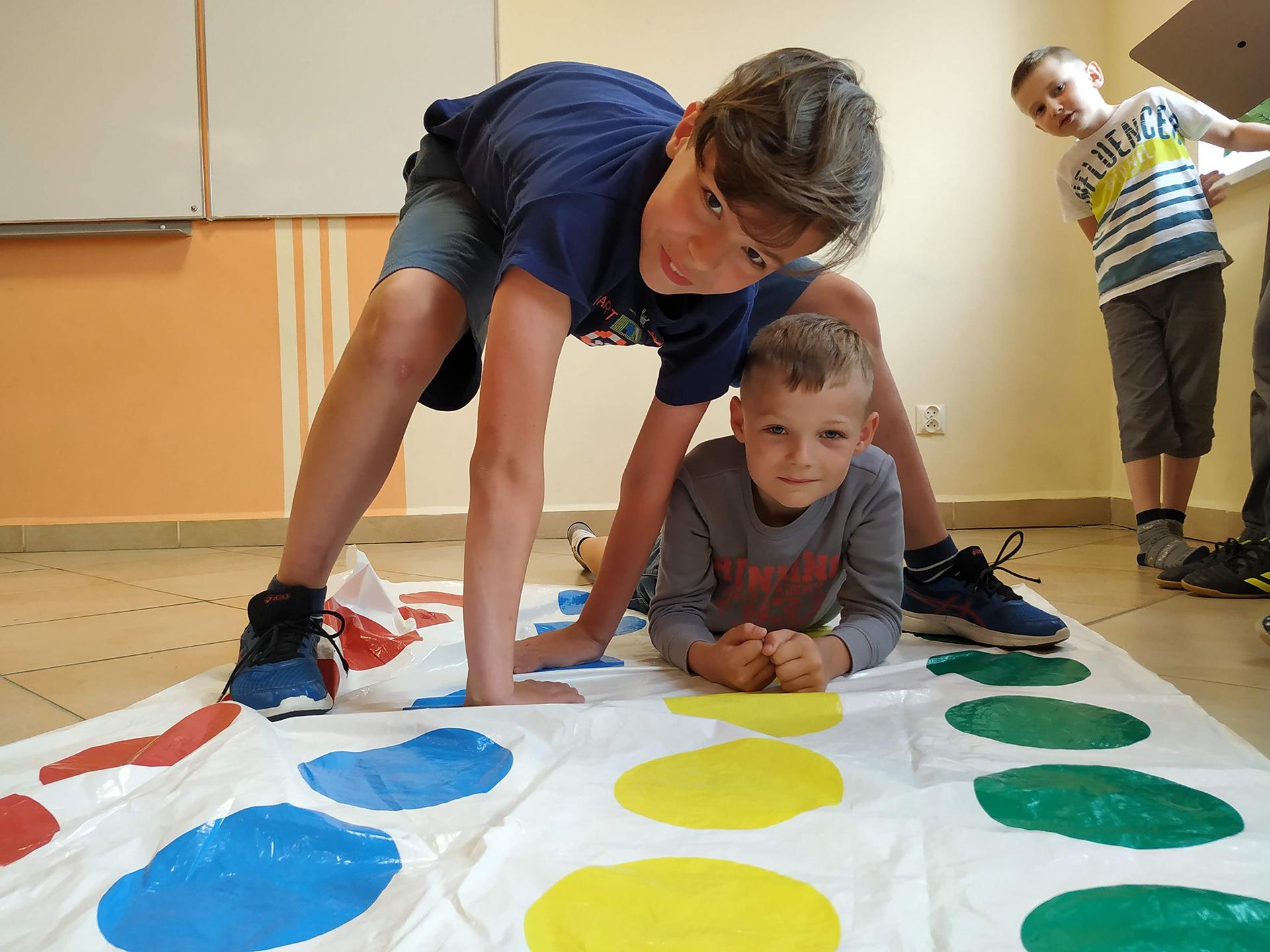 Chłopcy grający w Twistera na półkolonii językowej w szkole językowej Bacalarus z Zamościa