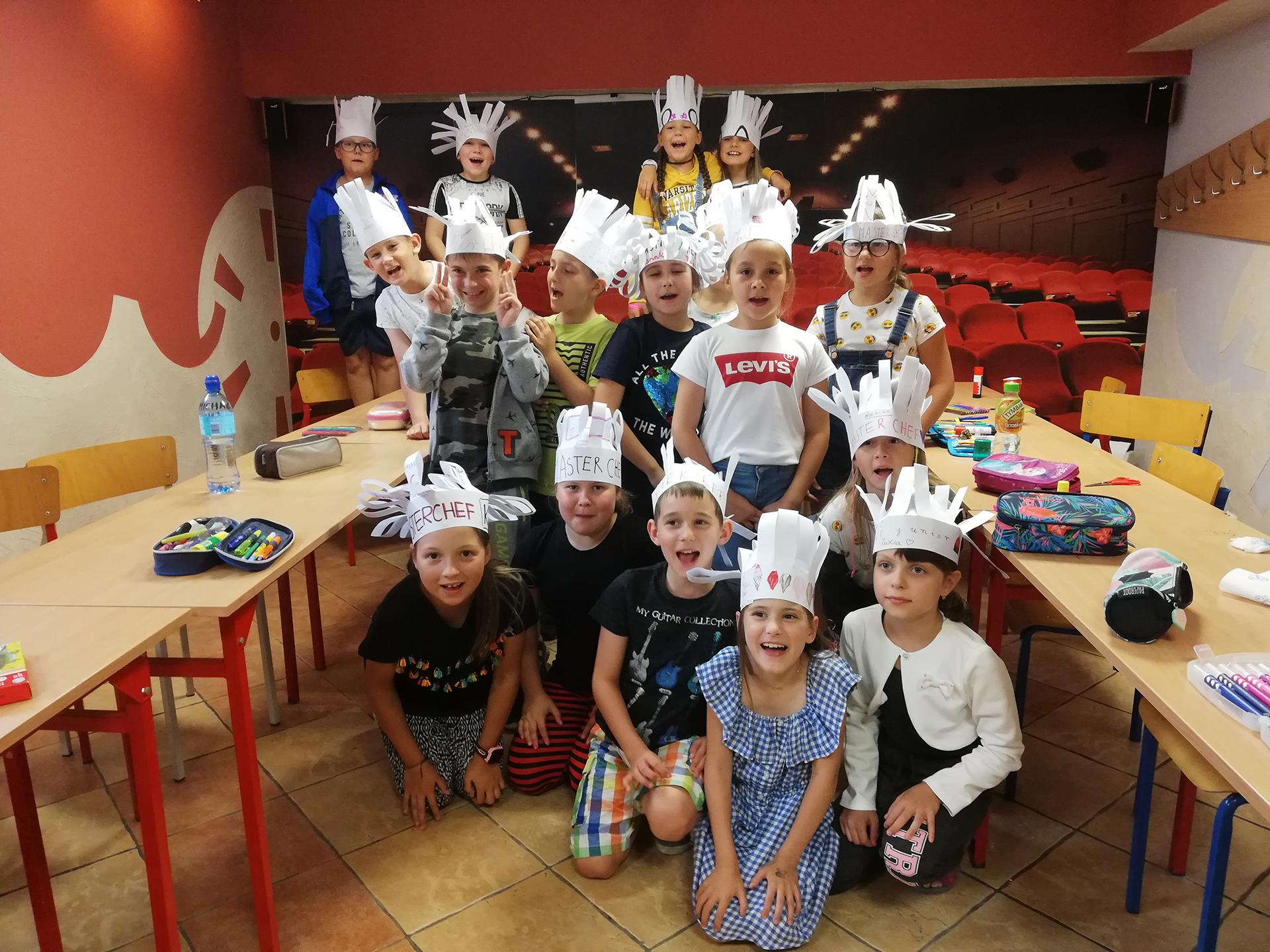 Dzieci z ręcznie wykonanymi kapeluszami podczas półkolonii językowej w Zamościu (szkoła językowa Bacalrus)